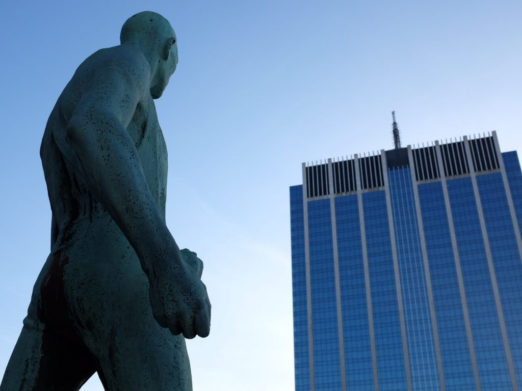 Statue staring down a large building